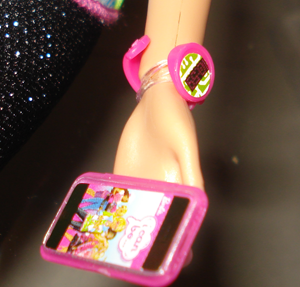 Close-up of her hand wearing a digital watch and holding an iPhone (or maybe a Touch).